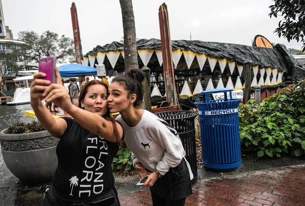 Tania Caceres, left, of Fort Lauderdale and friend Nallely Quinones, of Hallandale Beach take a selfie in front of The Gator in the Bay, a floating sculpture created by artist Lloyd Goradesky.