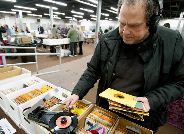 Record collector Stefan Luldburg, visiting from Sweden, listens to 45s on his portable record player at the Lehigh Valley Music Expo Vinyl, DVD & CD Collectors Show at Merchants Square Mall in Alentown.