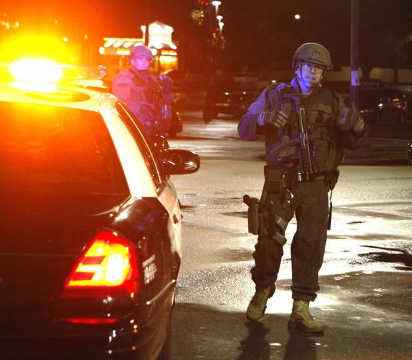 A Los Angeles County sheriff's deputy gears up with a partner to drive into position in La Crescenta where a man barricaded himself in a Verizon store and killed himself on Friday, Nov. 29, 2013.