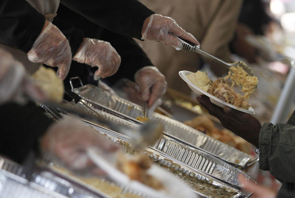Daily Press File photo: Volunteers fill up plates with thanksgiving food during the Feeding 5000 Thanksgiving Harvest and Community Celebration event at the Farmer's Market in Newport News on Saturday, November 17, 2012