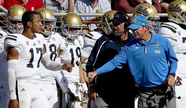 UCLA quarterback Brett Hundley and Coach Jim Mora go for a fist-bump during a game on Oct. 19.