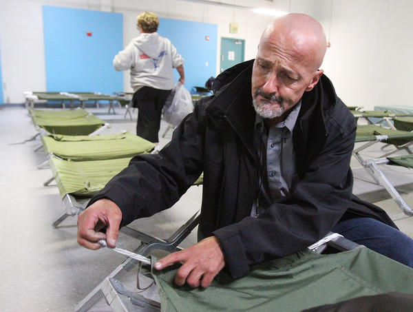 "Arthur Morris, who has been homeless about one year, pulls a small rope through the canvas of his cot to create a better sleeping surface at Ascencia in Glendale for the Glendale Winter Shelter Program on Monday, December 2, 2013. He does this because the metal bars that used to be there were once used as a weapon and have since been removed from all the cots making them a little short, and difficult to contain a pillow. Morris' comment was, ""Don't complain about it. Figure out a way to solve it,"" which is why he came up with this solution to his cot, which other people in the room thought was pretty smart. The shelter opened last night for a handful of people, but the 80 bed capacity is expected to fill if it rains in the next couple days. (Tim Berger/Staff Photographer)"