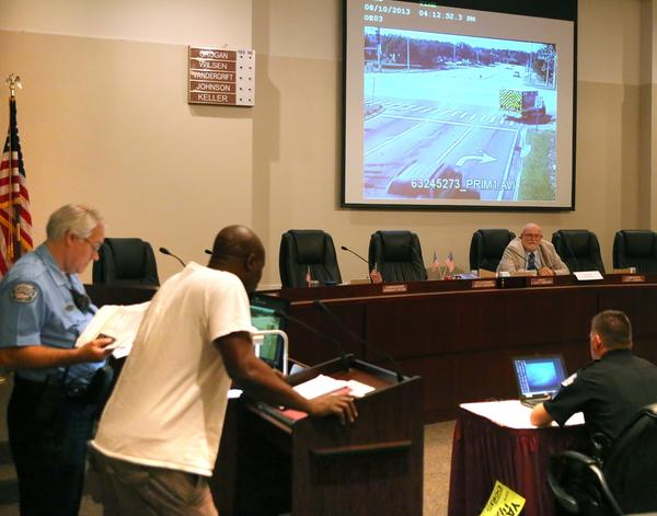 Ocoee hearing officer Fred Wilsen, seated in front of the screen, talks with a driver appealing a ticket for running a red light. Video of the incident captured by a red-light camera plays on the screen behind him.