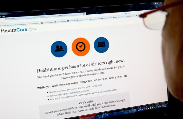A woman reads a message indicating that the HealthCare.gov insurance marketplace website has too much traffic to continue enrollment.