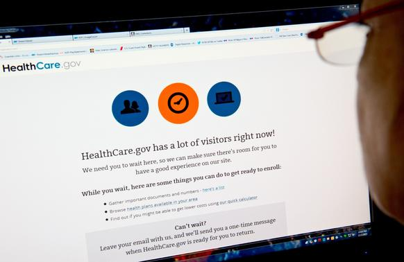 A woman in Washington reads a message indicating that the HealthCare.gov insurance marketplace Internet site has too much traffic to continue enrollment after the White House's deadline to have the site working for a majority of users.