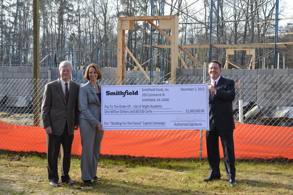 Isle of Wight Academy headmaster Benjamin Vaughan(left) and Mary-Margaret Wells, Isle of Wight Academy's director of development, accept a $1 million pledge from Larry Pope, president and CEO of Smithfield Foods, Inc.