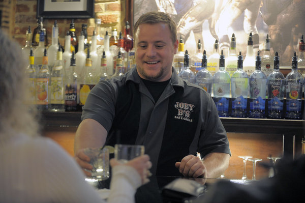 Joey B's Bar and Grille bartender William Drew serves a drink on a Saturday night.