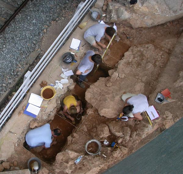Archaeologists are shown excavating a Neanderthal shelter at Riparo ...