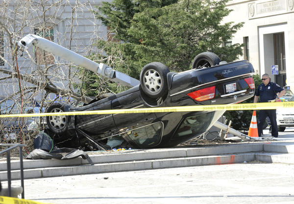 An overturned car sits outside Baltimore City Hall. Police say a pedestrian was struck and injured.