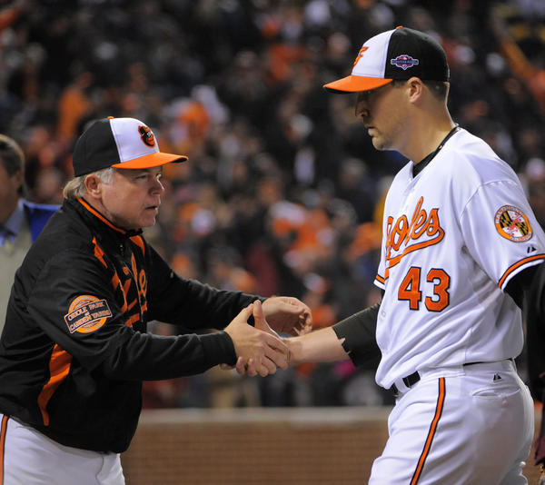 Former Orioles closer Jim Johnson shakes hands with manager Buck Showalter after the Orioles edged the New York Yankees, 3-2, in the ALDS last year.