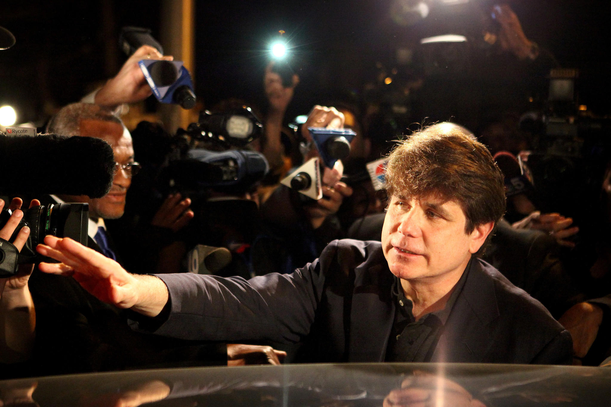 Former Gov. Rod Balgojevich is surrounded by members of the media as he leaves for prison.