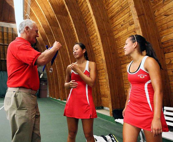 Parkland head coach George Grim (left) hands out the first-place medals to teammates Jenna Peng and Tuguyen Pham after winning the District 11 Class 3A Doubles Tennis Championships in October.