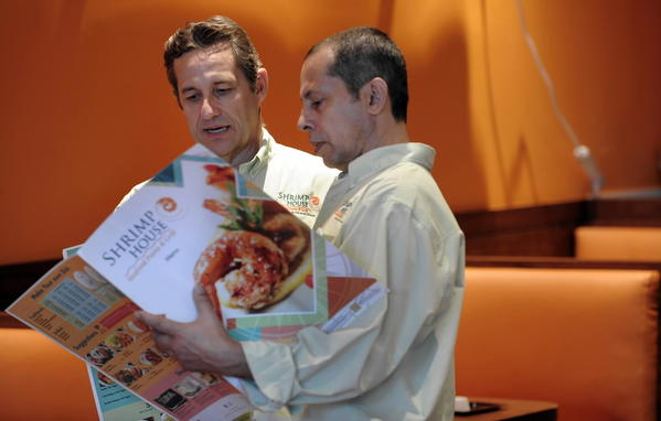 Shrimp House restaurant Shift Managers, Nelson de Souza, right, and Altair Barreiro discuss items on their menu before the grand opening party of their new restaurant.