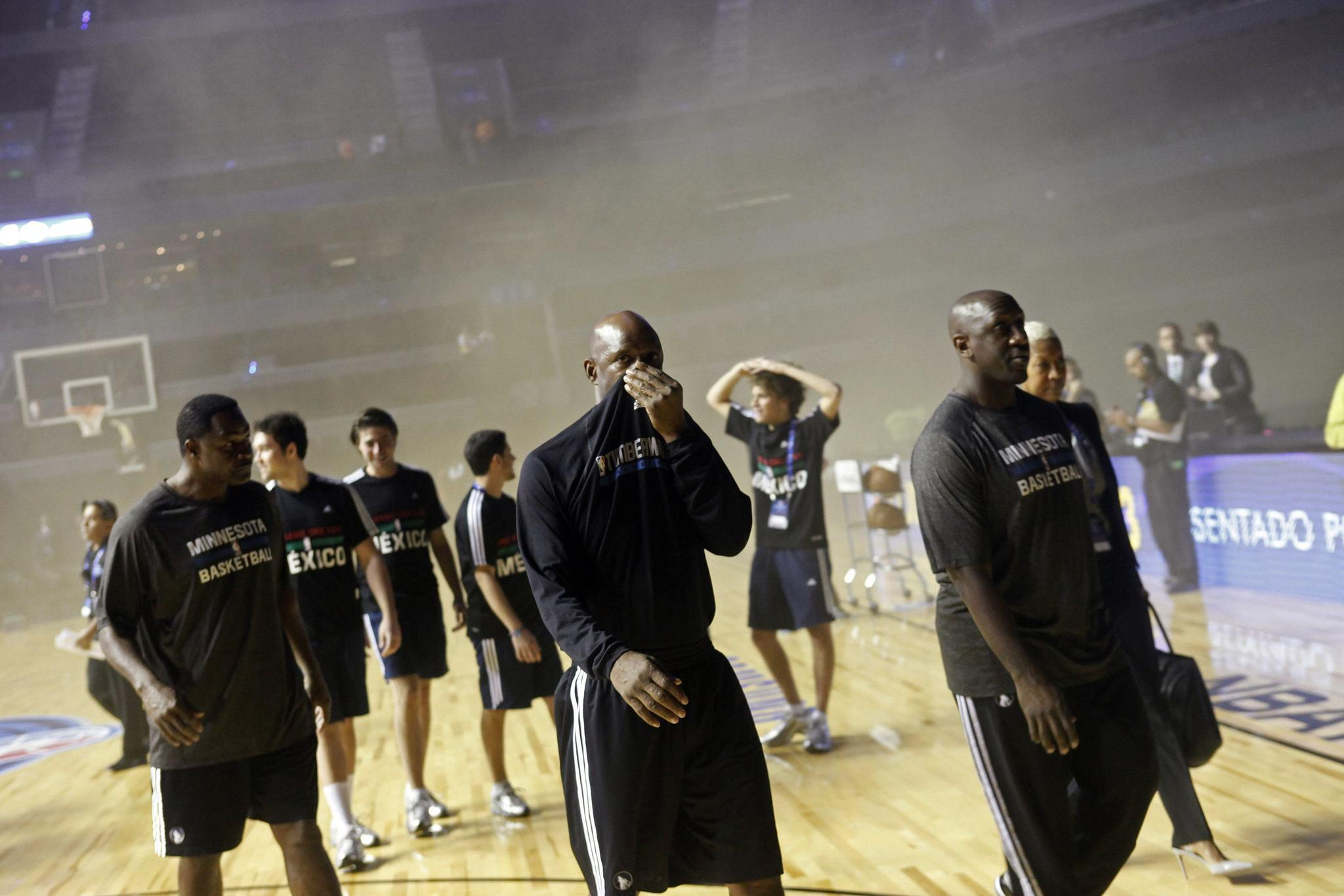 Timberwolves players walk off the court amidst smoke at the Mexico City Arena in Mexico City.