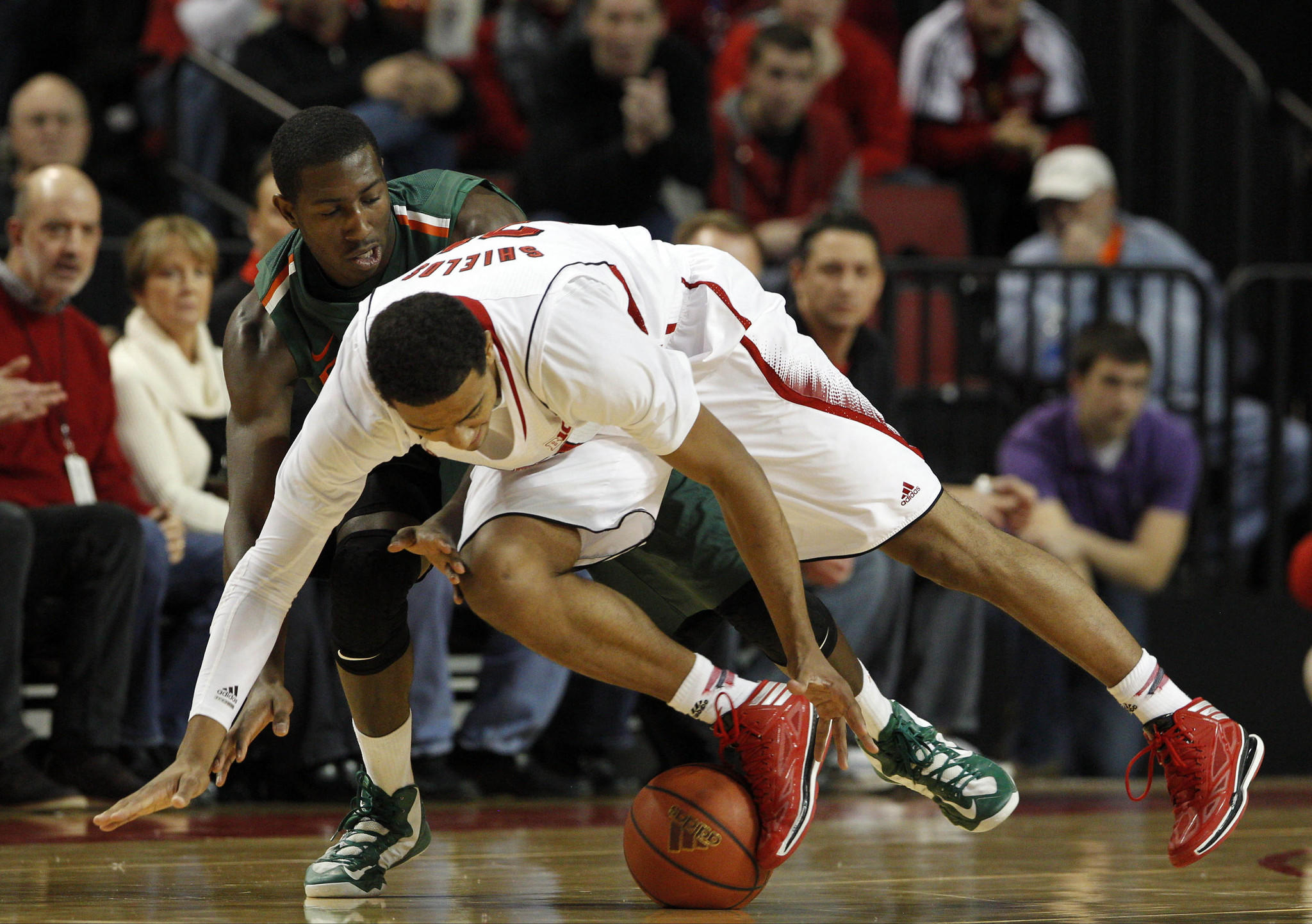 Nebraska's Shavon Shields and Miami's Davon Reed chase the loose ball in the first half.