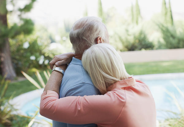 Older couple hugging in backyard
