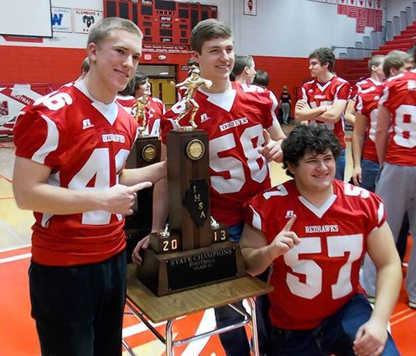 Naperville Central juniors Billy Gammon (46), Mack Heatherly (58) and Hayden Saldivar (57) pose with their state championship trophy following Wednesday's recognition assembly at the school.
