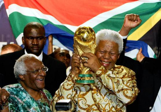 Former South African President Nelson Mandela holds the Jules Rimet World Cup beside Capetown Archbishop Desmond Tutu at the FIFA headquarters in Zurich.