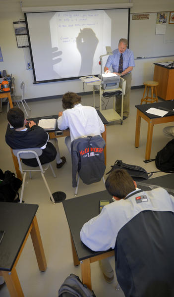 Science teacher, Bob Mahon works through problems with his freshman physics class.