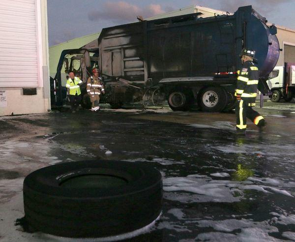 A trash hauler caught fire, injuring a passenger