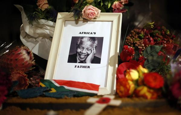 Flowers and tributes are left on the Nelson Mandela statue on Parliament Square in London December 6, 2013.