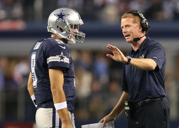Cowboys quarterback Tony Romo talks with coach Jason Garrett during a timeout.