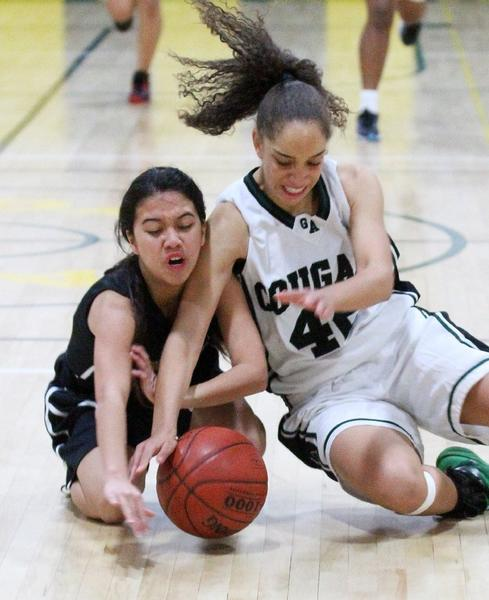 Holy Family's Alexandra Mata and Glendale Adventist's Harley Federici battle for possession in the first half of a nonleague girls' basketball game at Glendale Adventist Academy on Thursday. (Tim Berger/Staff Photographer)