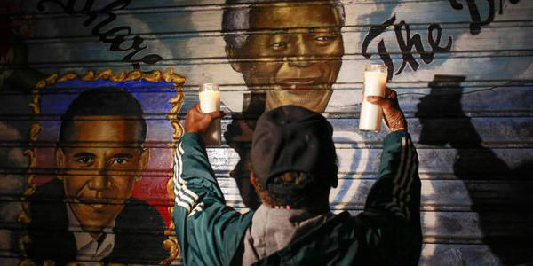 A man holds candles in front of a mural of former South African President Nelson Mandela in New York. Mandela died peacefully at his Johannesburg home after a prolonged lung infection. (Shannon Stapleton, Reuters)