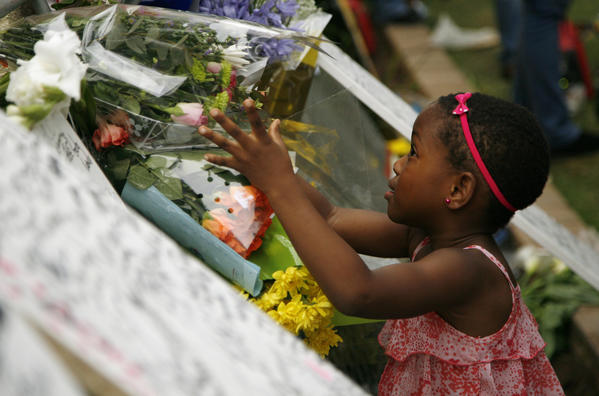 A young girl places flowers outside the home of former South African President Nelson Mandela in Johannesburg.