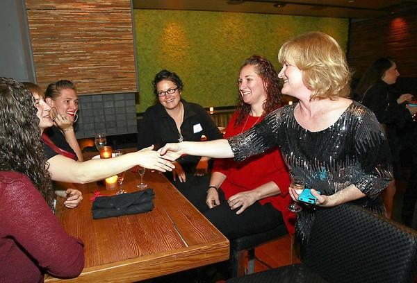 Katrina Foley, right, welcomes guests to her annual holiday party at Mesa restaurant on Wednesday.