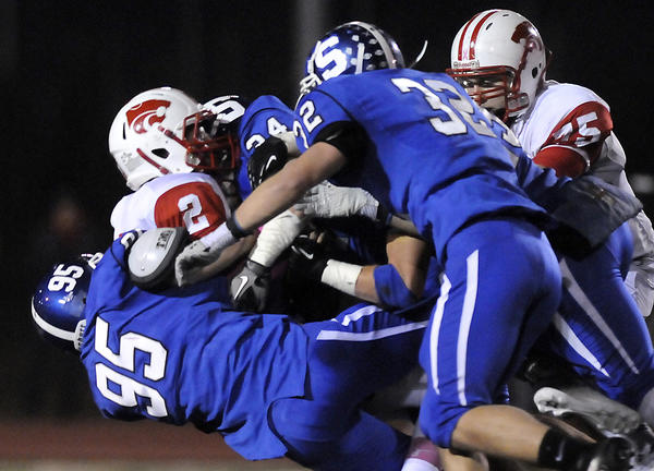 The Southington defense, including Zach Maxwell (right), swarms to the ball.