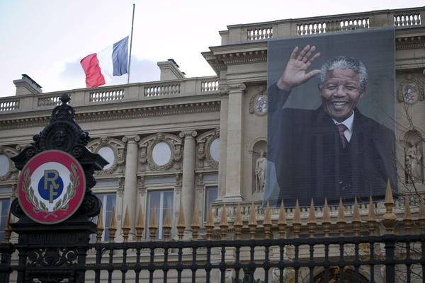 A giant portrait of late South African President Nelson Mandela hangs on the facade of the French Foreign Ministry in Paris. Flags lowered to half-staff, days of mourning and other tributes to the anti-apartheid fighter, who died Thursday at his home in a Johannesburg suburb, have poured out from every corner of the world.