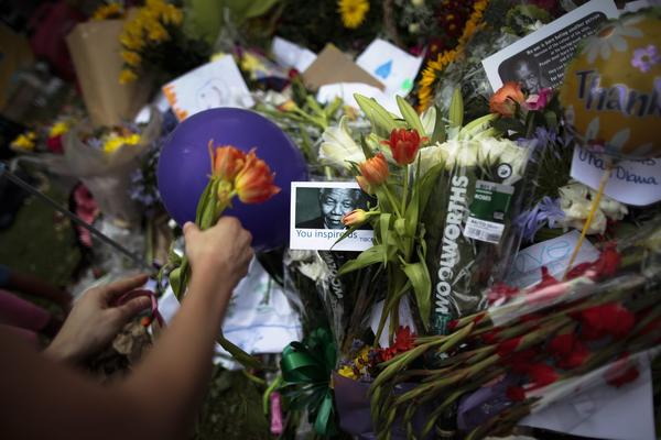 Mourners leave flowers outside the house of South Africa's late former President Nelson Mandela in the Johannesburg suburb of Houghton.
