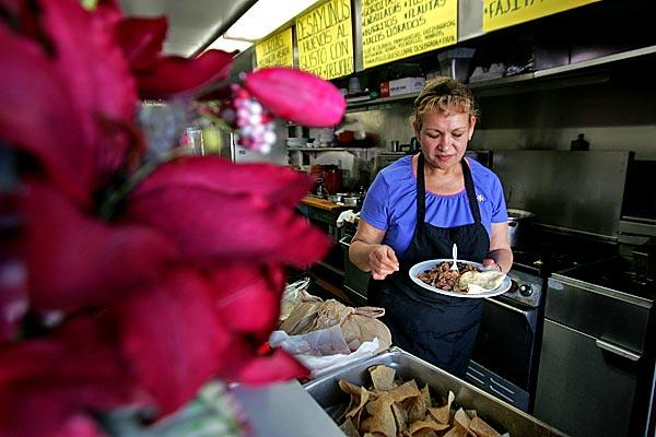 Carmen Ortega prepares a meal in her new restaurant.