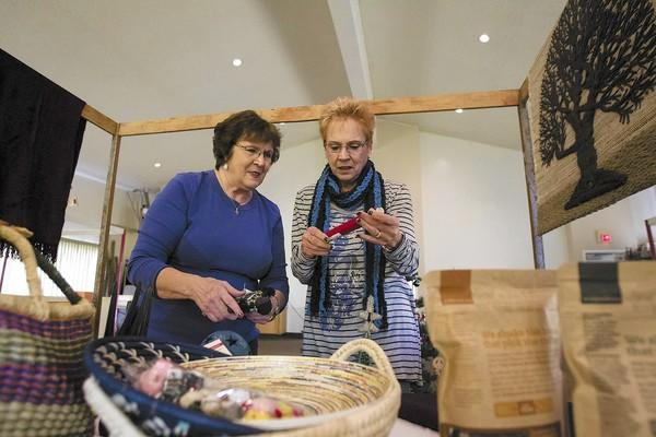 Nan Collett, left, and Jeanne Funnell with the Harbor Christian Church set up for a holiday gift bazaar featuring goods made by Third World artisans on Friday.
