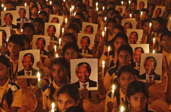 Schoolchildren hold candles and portraits of former South African President Nelson Mandela during a prayer ceremony at a school in the southern Indian city of Chennai December 6, 2013.