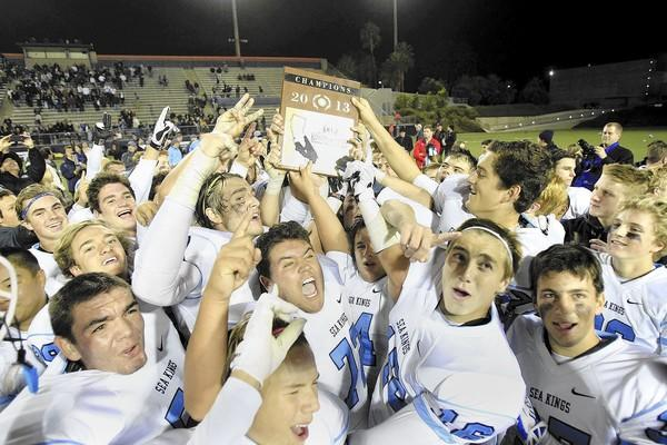 Corona del Mar High football players celebrate as they hold up their third straight championship plaque after beating Garden Grove, 42-21, in a CIF Southern Section Southwest Division championship game at LeBard Stadium in Costa Mesa on Friday.