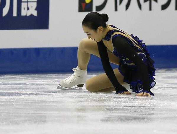 In a picture summing up the day for women's figure skating, Mao Asada of Japan after her fall during the women's free skate at the Grand Prix Final in Fukuoka, Japan, where Asada won.