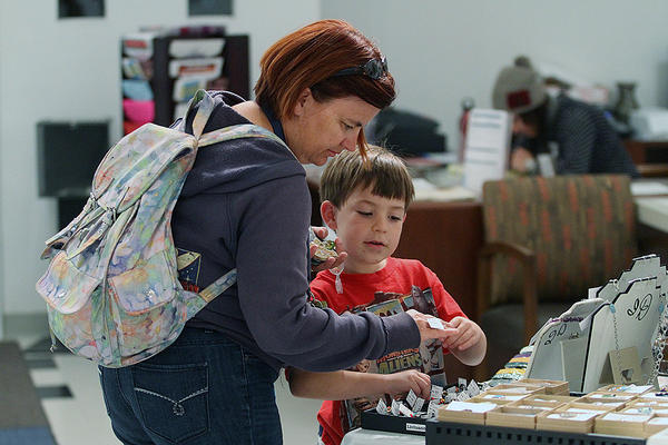 Melanie Paige, of Sunland, with her son Marcus, 6, shop for crystal jewelry at the Creative Arts Center 2013 Holiday Arts & Crafts Boutique on Friday, December 6, 2013. All the items are produced by local artists who get an 85% split of the sale if their artwork sells. The other 15% goes to the Burbank Fine Arts Federation.