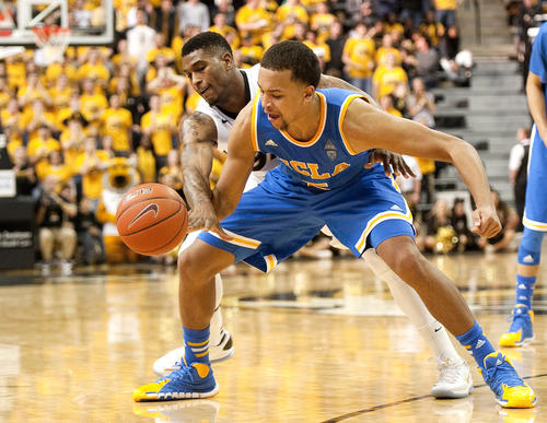 UCLA guard Kyle Anderson tries to control the ball as Missouri guard Earnest Ross takes a swipe at it in the second half Saturday.
