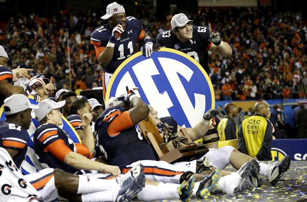 Auburn players pose with a Southeastern Conference sign after defeating Missouri in the SEC title game on Saturday.