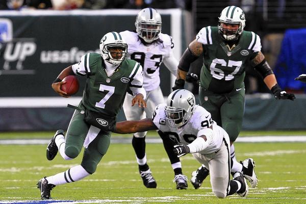 New York Jets quarterback Geno Smith (7) avoids a tackle by Oakland Raiders linebacker Kaelin Burnett during the second half at MetLife Stadium. The Jets defeated the Raiders 37-27.
