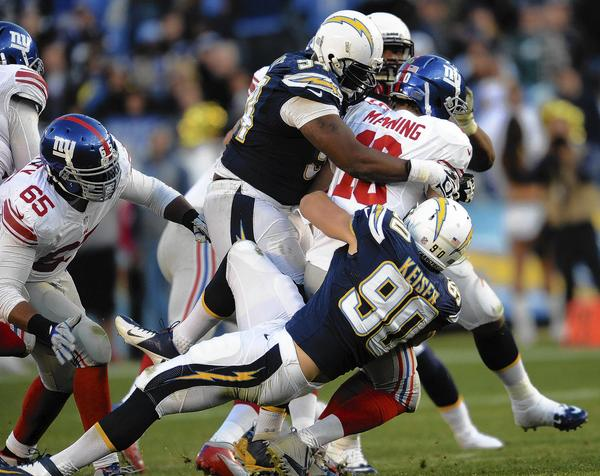 San Diego Chargers linebacker Thomas Keiser (90) and defensive end Corey Liuget (94) sack New York Giants quarterback Eli Manning in the fourth quarter at Qualcomm Stadium.
