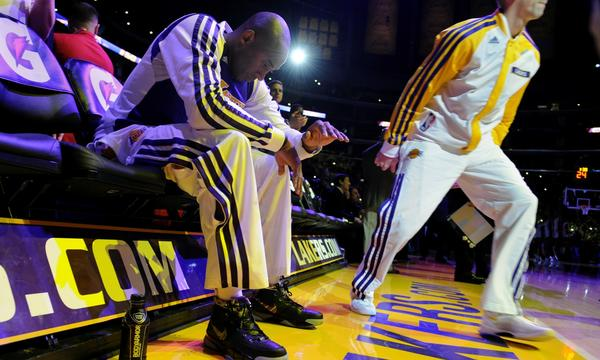 Lakers star Kobe Bryant sits on the bench as he's introduced before the start of Sunday's game against the Toronto Raptors. Bryant struggled in his return from a torn Achilles' tendon as the Lakers lost, 106-94.