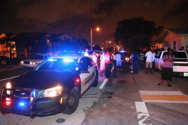 Investigators and neighborhood residents gather late Sunday night, Dec. 8, 2013, along the 300 block of Northwest 12th Court in Pompano Beach where a man was found dead on the pavement after reports of gunfire.