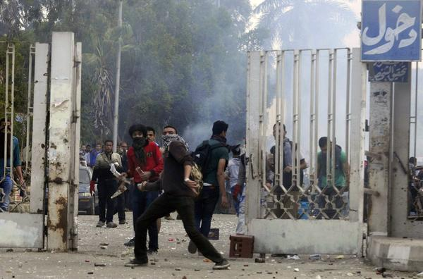 Al Azhar University students who support Egypt's Muslim Brotherhood clash with riot police outside the school's Cairo campus Monday.