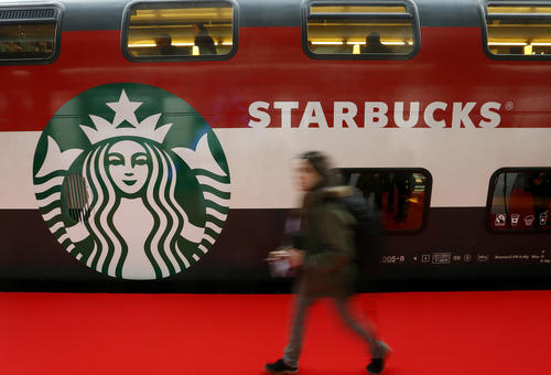 A woman walks past a Starbucks logo painted on a railway coach at the main train station in Zurich November 14, 2013.