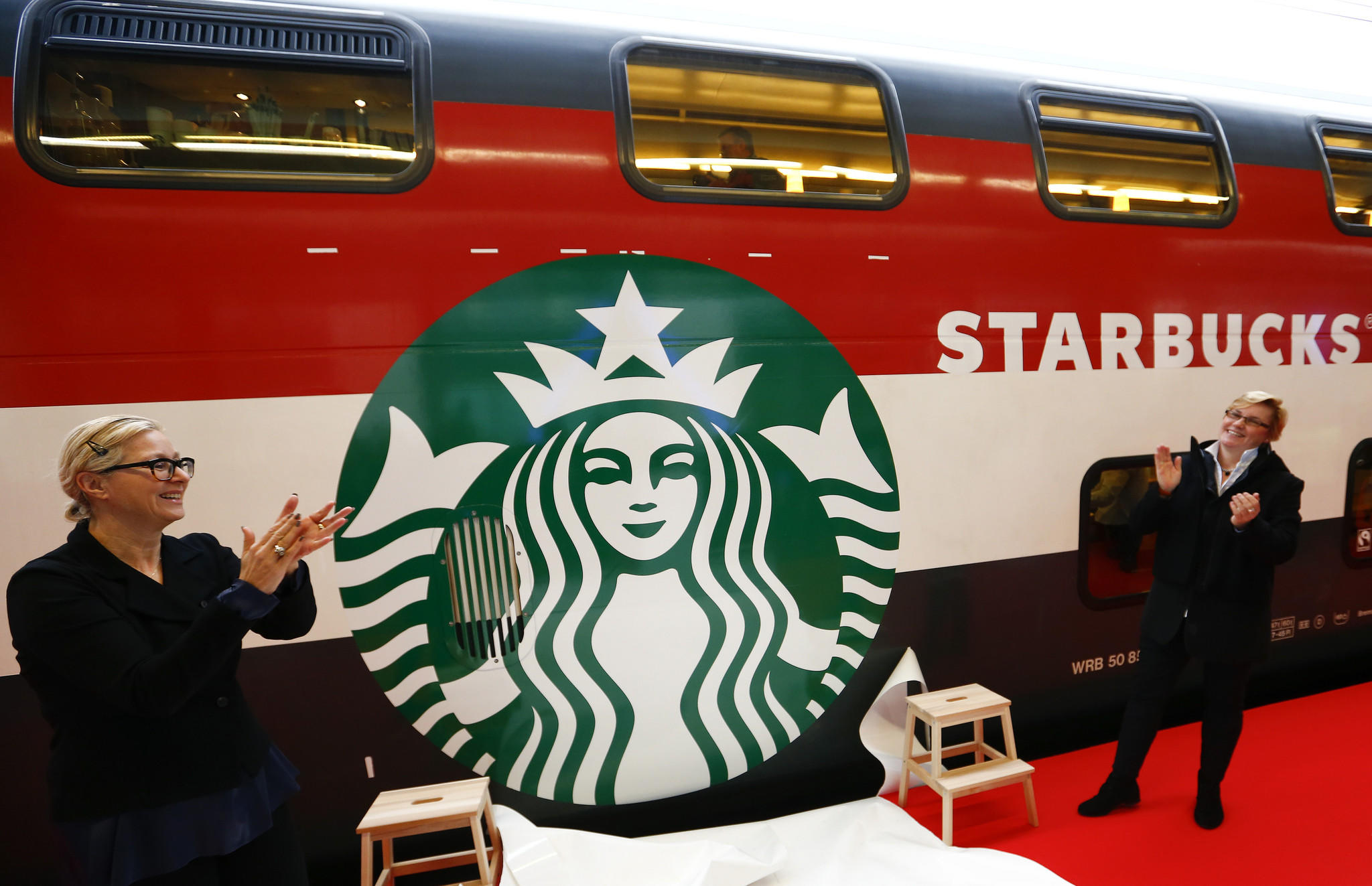 Jeannine Pilloud, head of passenger transportation of Swiss rail operator SBB and Liz Muller (R), director Global Concept Design Starbucks applaud after they unveiled the Starbucks logo painted on a railway coach at the main train station in Zurich November 14, 2013.