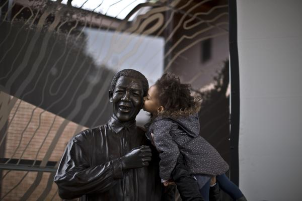 A girl held up by her mother kisses a statue of the late Nelson Mandela in Johannesburg, South Africa.