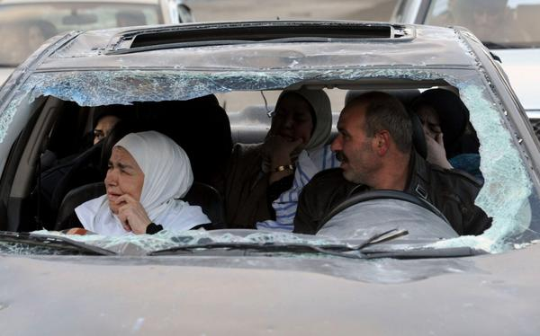 Syrians sit inside a damaged vehicle after forces loyal to President Bashar Assad's regime captured the town of Nabek, northeast of Damascus.